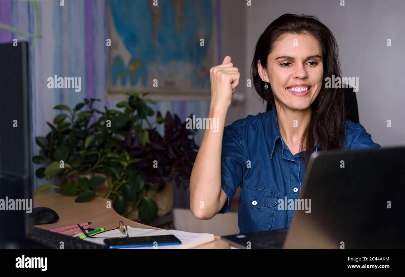 Une jeune femme surjoyeuse en denim travaillant à la maison avec un ordinateur portable et en étirant les bras pour obtenir de bonnes nouvelles ou gagner du succès. Carte du monde dans Banque D'Images