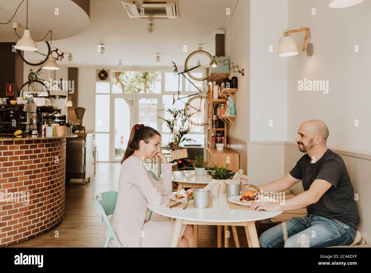 Homme et femme souriants assis à une table dans un café Banque D'Images