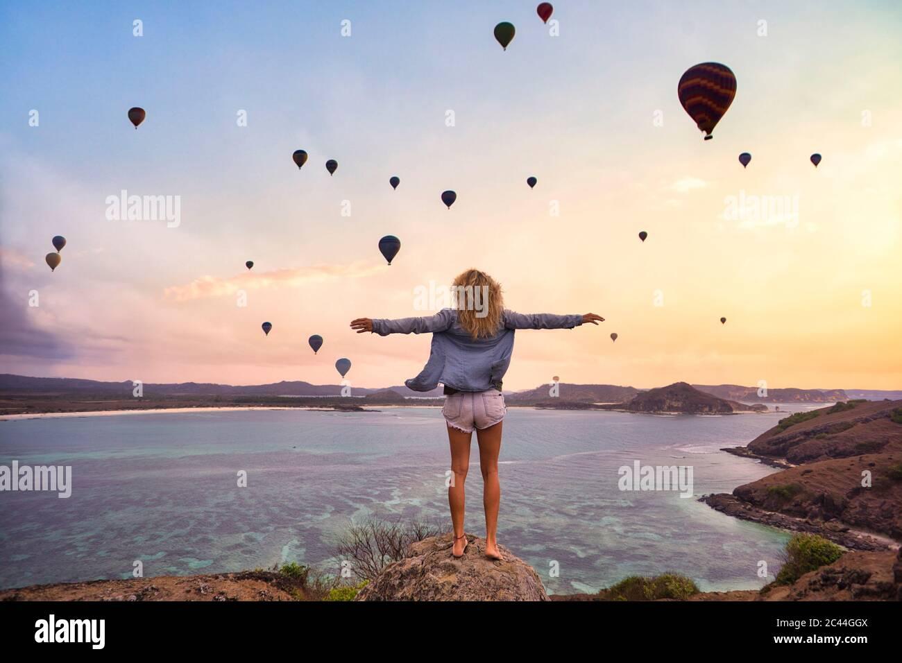 Indonésie, Nusa Tenggara Ouest, ballons à air chaud volant au-dessus d'une femme seule debout sur la côte rocheuse avec des bras levés Banque D'Images