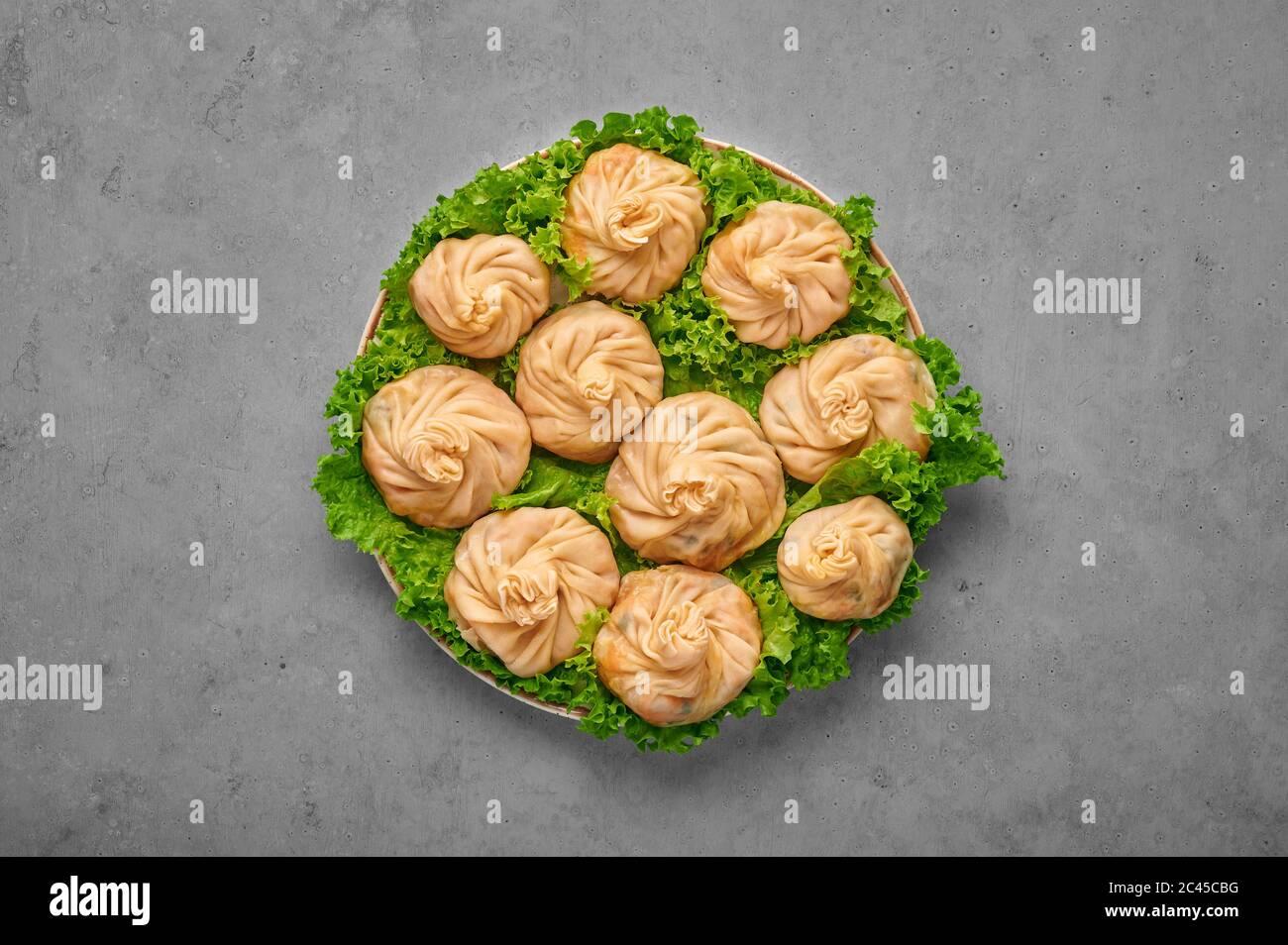 Veg Momos sur table en béton gris . Momos est le plat populaire de cuisine indienne, tibétaine, chinoise. Cuisine asiatique. Repas végétarien. Vue de dessus Banque D'Images