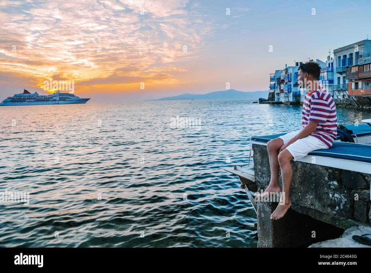Jeune homme en vacances à l'île grecque de Mykonos, des hommes se détendant dans le petit village de venise de l'île de Mykonos Banque D'Images
