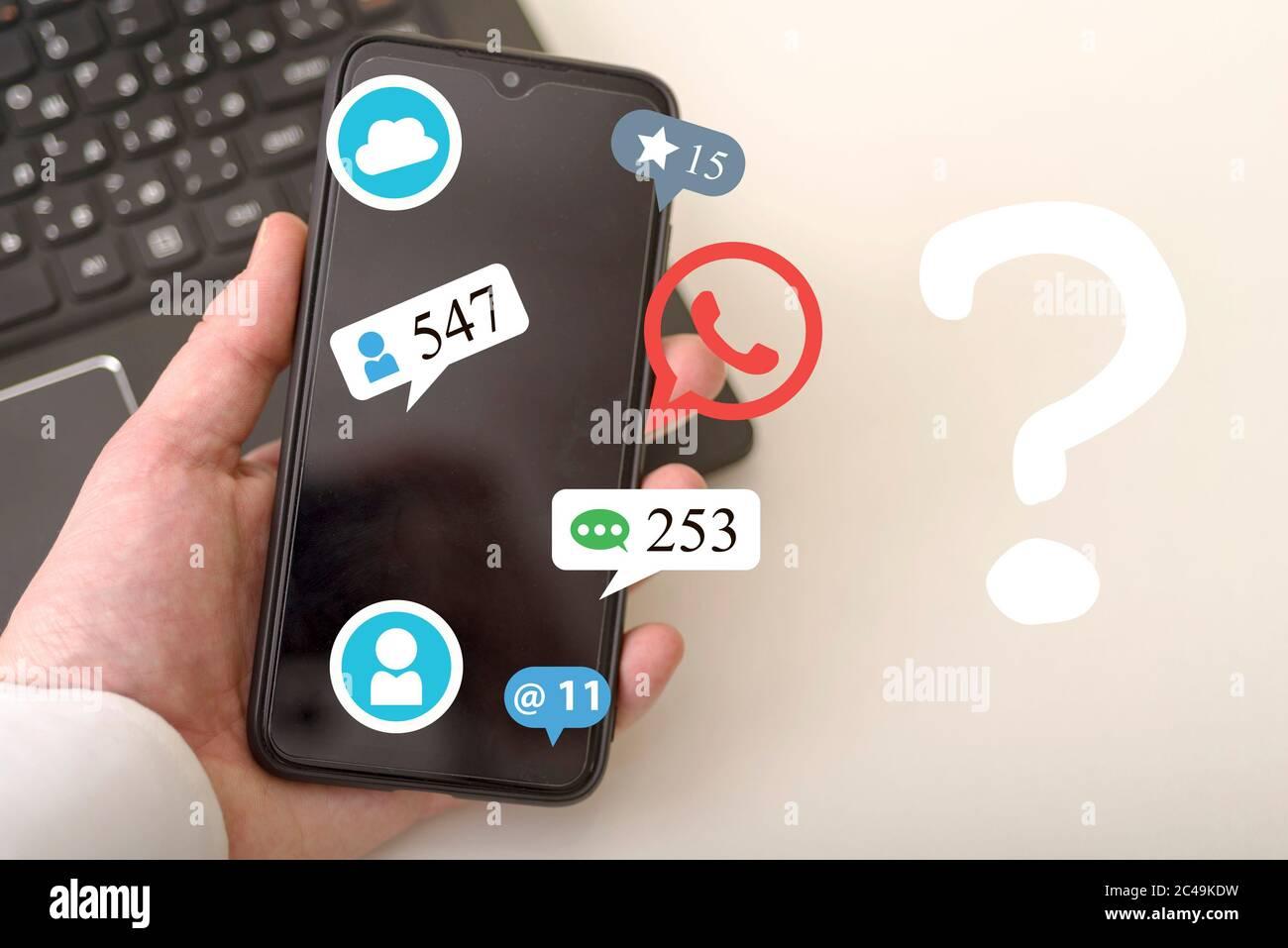 La main utilise un smartphone et un hologramme de diverses icônes, dont un point d'interrogation. Concepts de réseaux sociaux. Banque D'Images