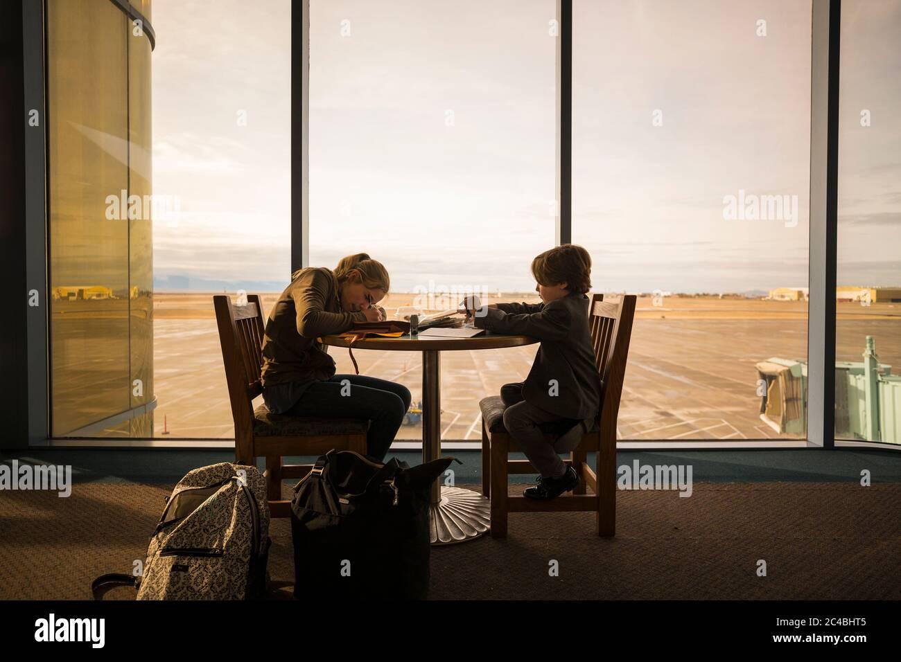 Un garçon et sa sœur aînée s'asseoir à une table dans un salon de l'aéroport, écrire et dessiner. Banque D'Images