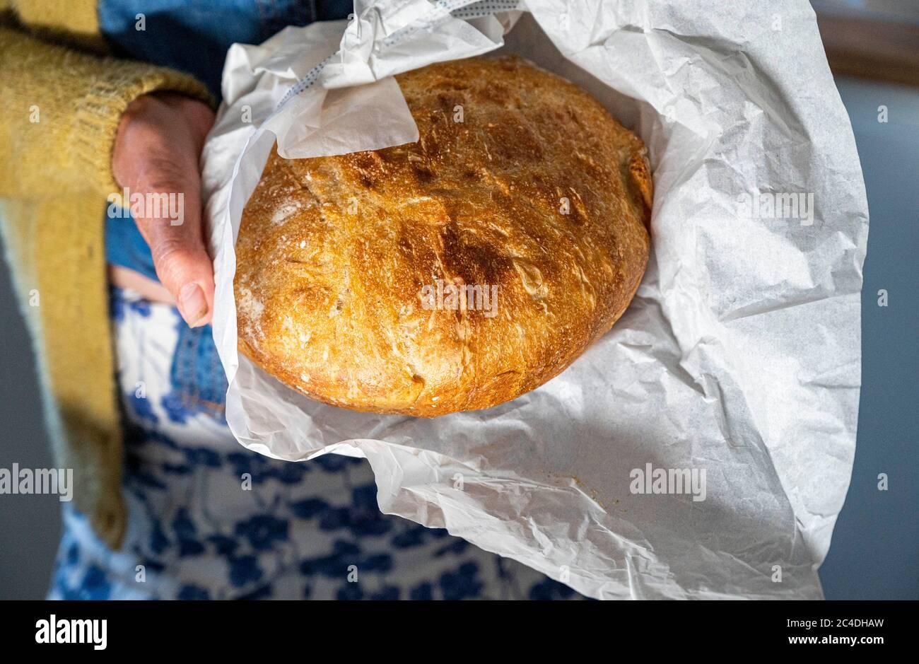 Pain de levain maison avec couteau à pain sur planche à découper photo prise par Simon Dack Banque D'Images