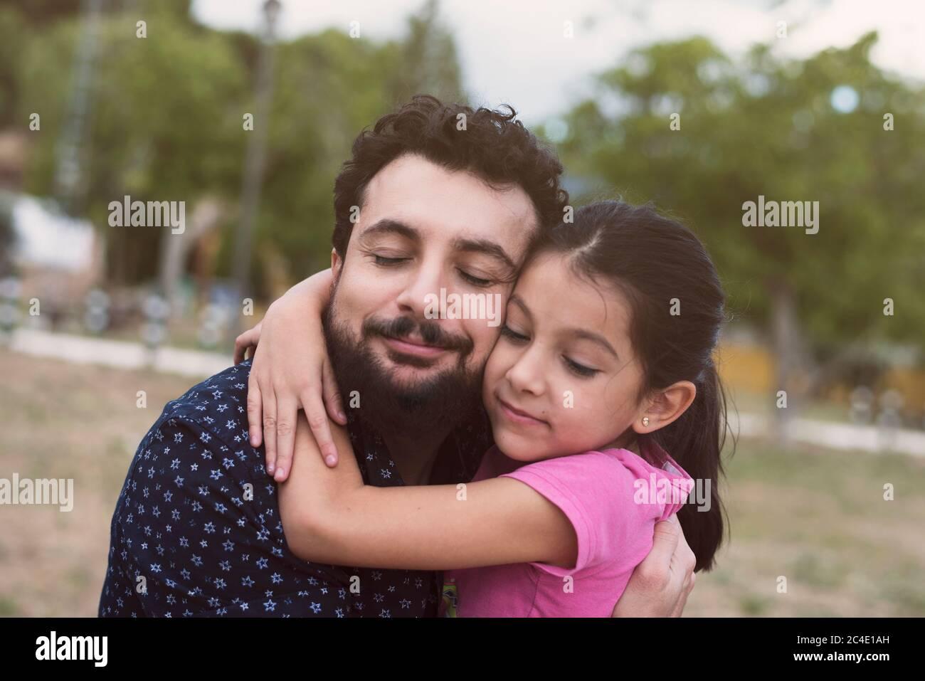 Père et petite fille grande accolade dans l'image à l'extérieur dans le parc Banque D'Images