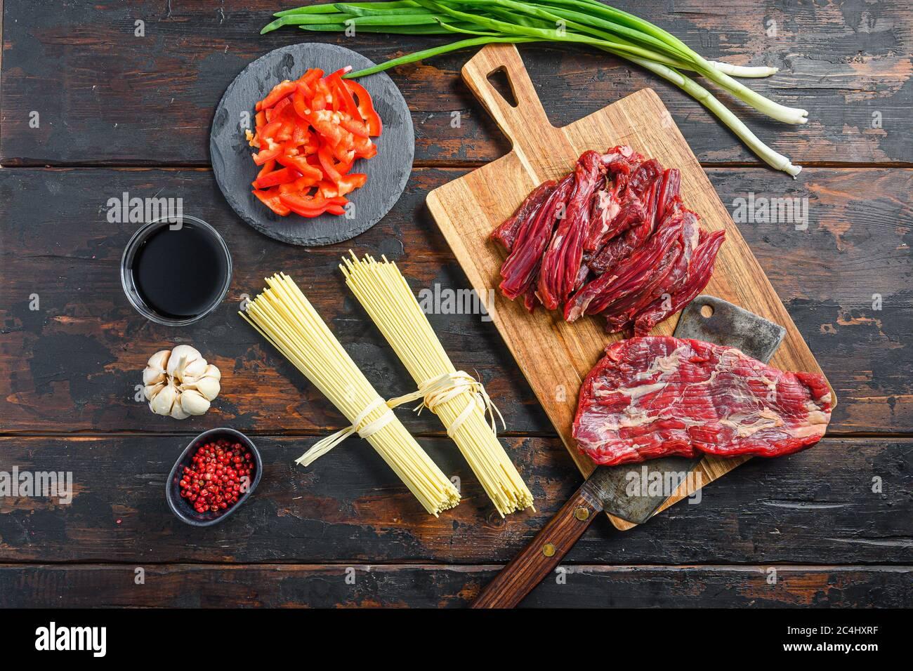 Ingrédients de cuisson pour les nouilles sautées avec légumes et bœuf . Steak et nouilles à la machette sur fond de bois Banque D'Images