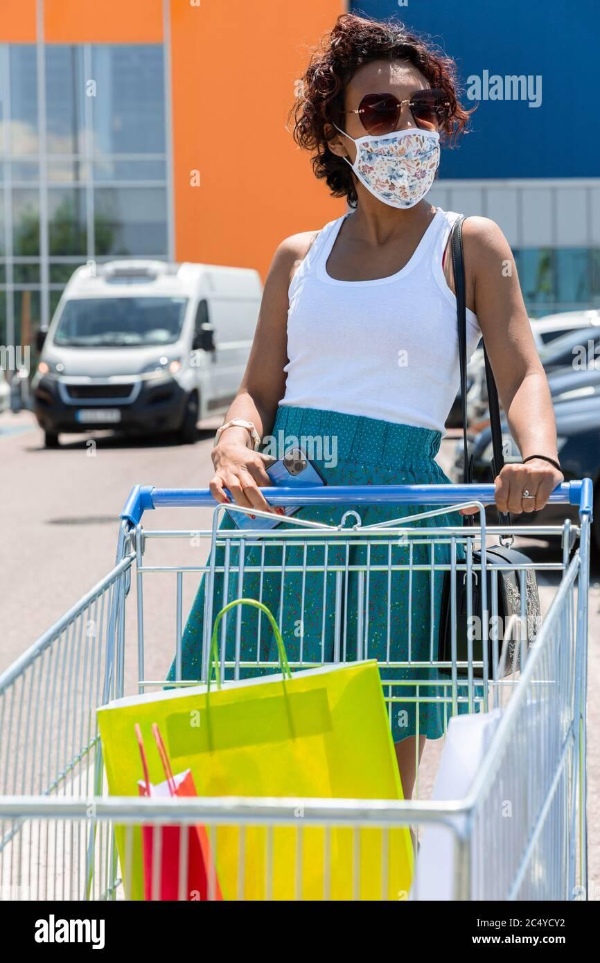 Femme portant un masque de protection poussant le chariot dans le stationnement du centre commercial. Concept de shopping dans la nouvelle norme. Banque D'Images