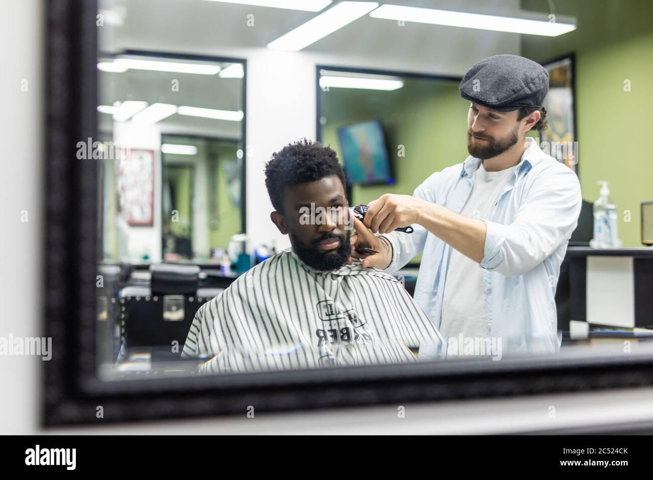 Jeune homme noir heureux en train d'être tondu avec une tondeuse électrique dans un salon de coiffure. Concept de soins de beauté pour hommes. Jeune homme africain souriant, qui devient nouveau Banque D'Images