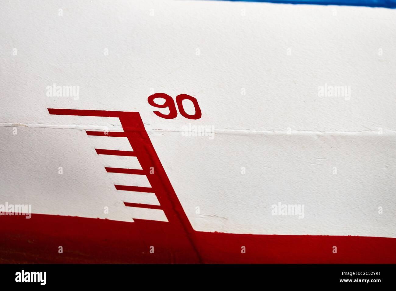 Marquage de la profondeur de l'eau sur la coque d'un navire avec le numéro « 90 », rouge et blanc Banque D'Images
