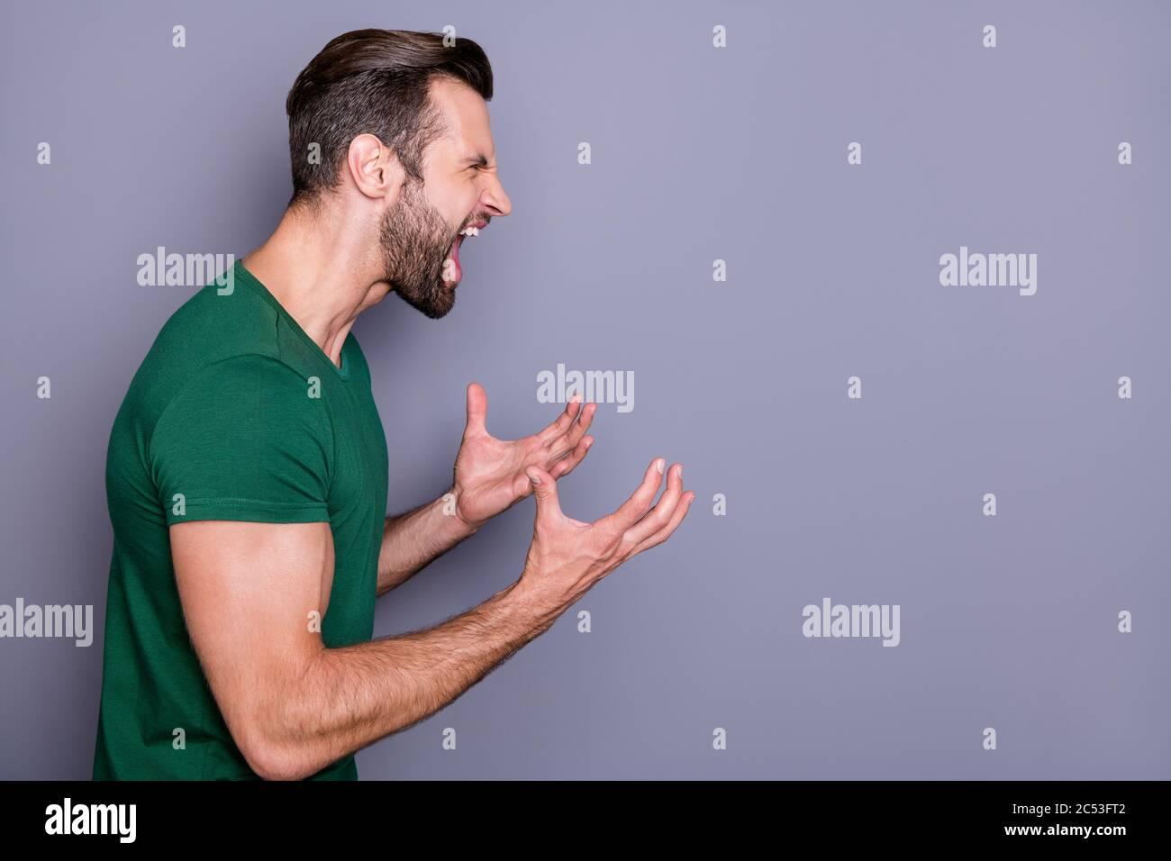 Profil photo de l'attrayant fou gars soigneux cheveux soil lever les bras yelling furieux côté vide espace combat avec petite amie porter décontracté vert t Banque D'Images