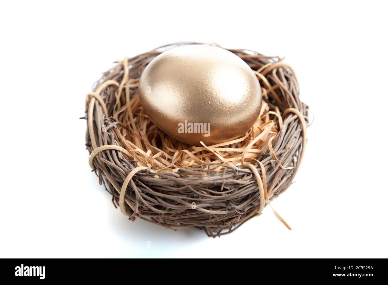 Un œuf d'or en nid sur fond blanc Banque D'Images