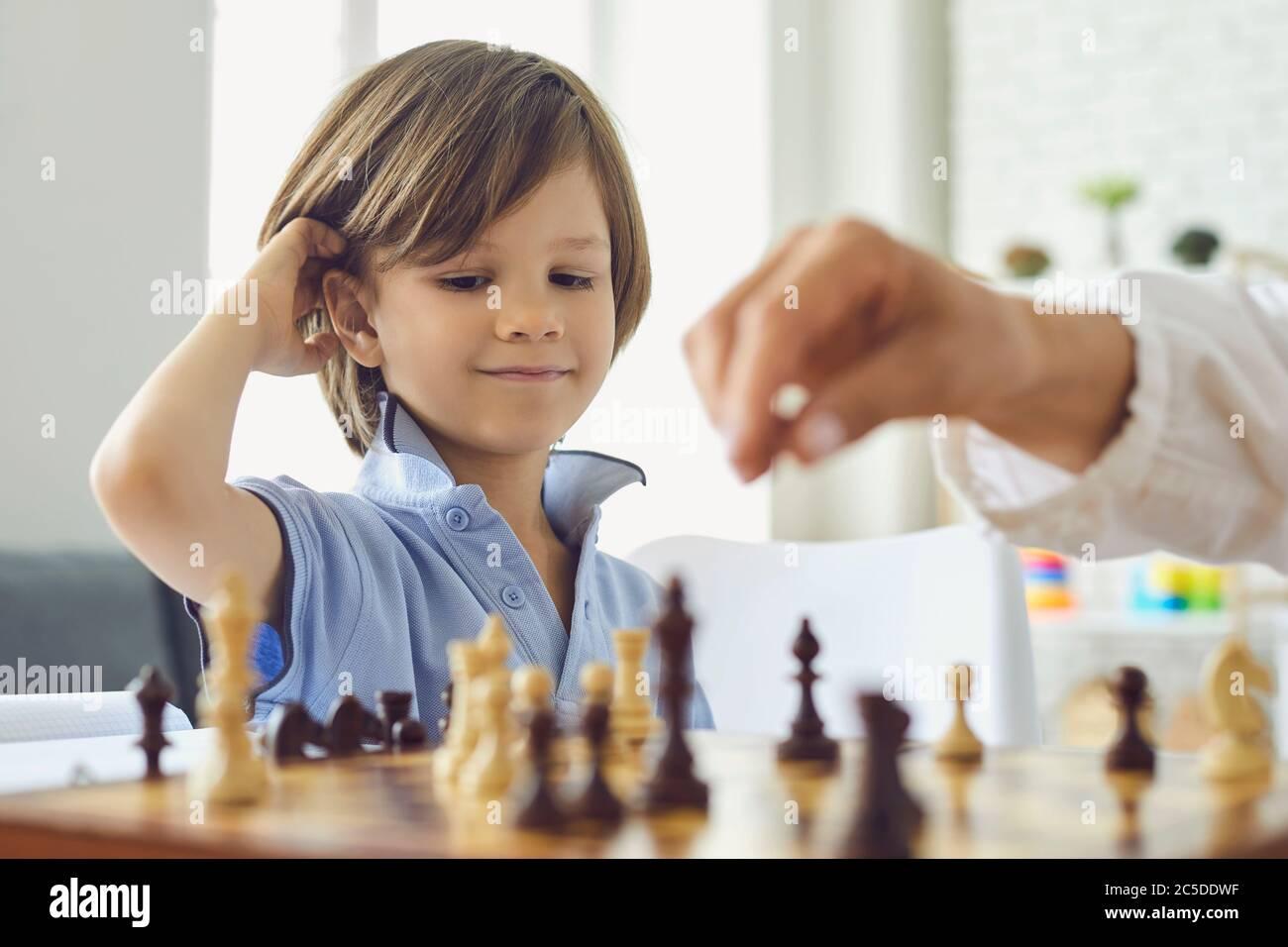 Adorable petit garçon jouant aux échecs avec sa mère à la maison. Enfant mignon appréciant jeu de stratégie de plateau avec ses parents à l'intérieur Banque D'Images