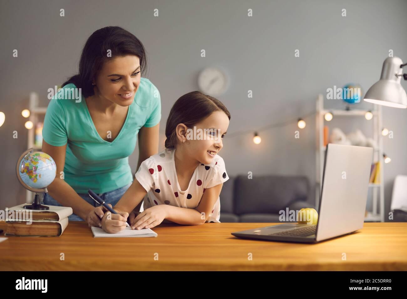 Mère et fille regardant la leçon professeur de conférence assis à distance à la table à la maison. Banque D'Images