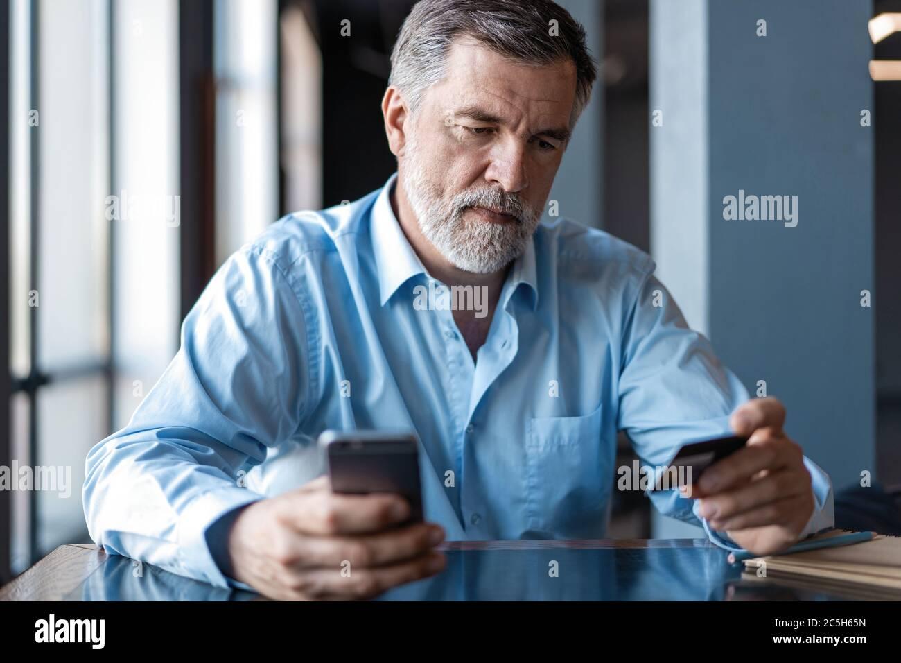 Paiement en ligne sur smartphone par mature Man. Beau chef d'entreprise mature assis dans un bureau moderne Banque D'Images