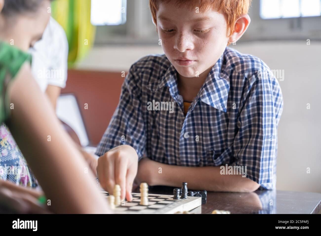 Joueur d'échecs sérieux de pensée et de mouvement de pièce à la maison - concept de la concentration de jeu d'enfant pendant le développement précoce, à la maison jeux éducatifs pour Banque D'Images