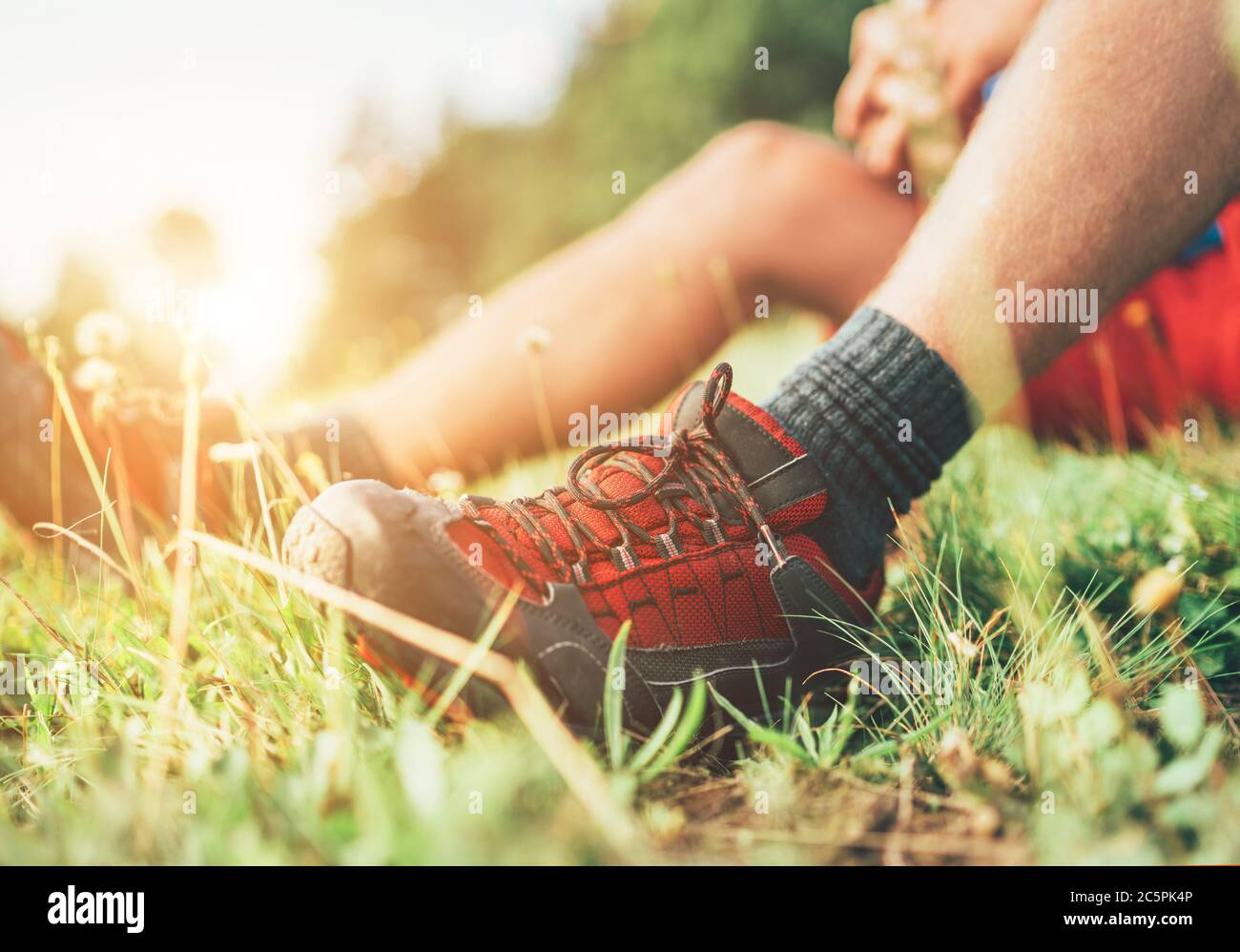 Chaussures de randonnée Backpacker gros plan. L'homme a une pause de repos assis sur l'herbe verte et appréciant la randonnée de montagne, sport actif Backpacking santé Banque D'Images