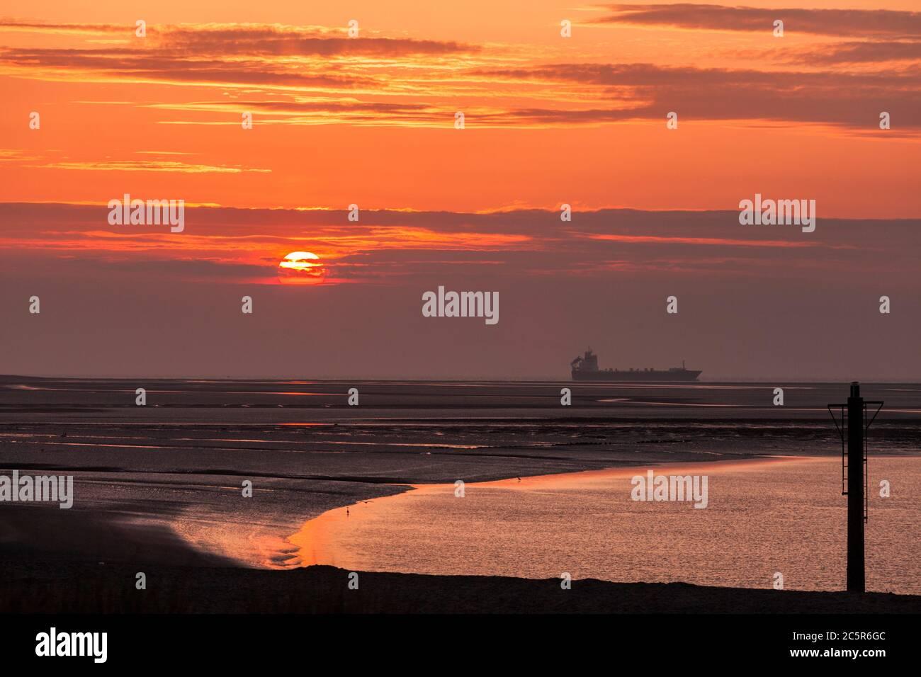 Vue sur la mer depuis Fleetwood sur la côte du Lancashire avec un bateau passant dans la mer irlandaise au coucher du soleil Banque D'Images