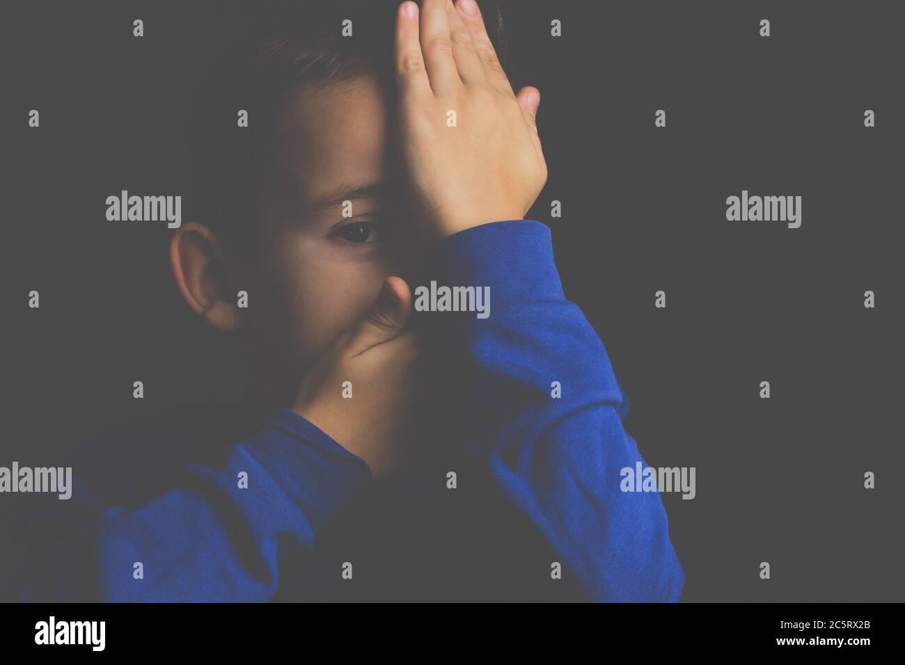 portrait d'un garçon aux cheveux sombres couvrant son visage avec ses mains sur un fond sombre Banque D'Images