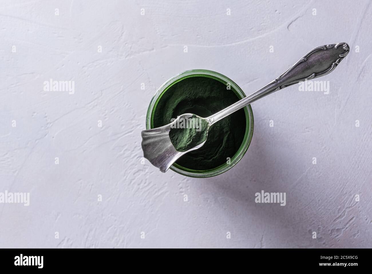 Poudre de chlorelle ou de spiruline verte naturelle dans un pot en verre rond et dans une cuillère en argent sur le bol. Concept de nourriture saine et de régime. Blanc Banque D'Images