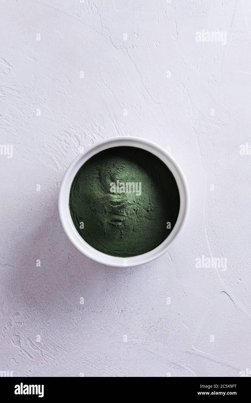 Poudre de chlorelle naturelle verte ou de spiruline dans un bol rond en porcelaine blanche directement au-dessus. Concept de nourriture saine et de régime. Tex blanc Banque D'Images