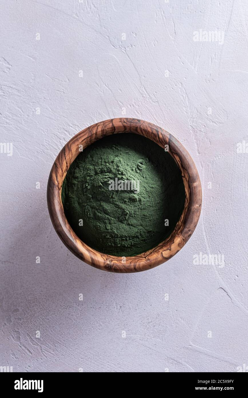 Poudre de chlorella ou de spiruline verte naturelle dans un bol rond d'olivier brun en bois, directement au-dessus. Concept de nourriture saine et de régime. W Banque D'Images