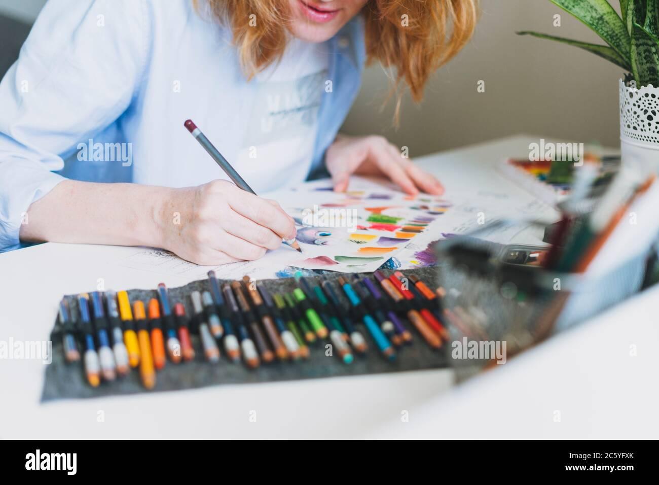 Rognez la photo de la jeune femme avec un illustrateur de cheveux rouges, l'artiste dessine à un bureau à la maison Banque D'Images