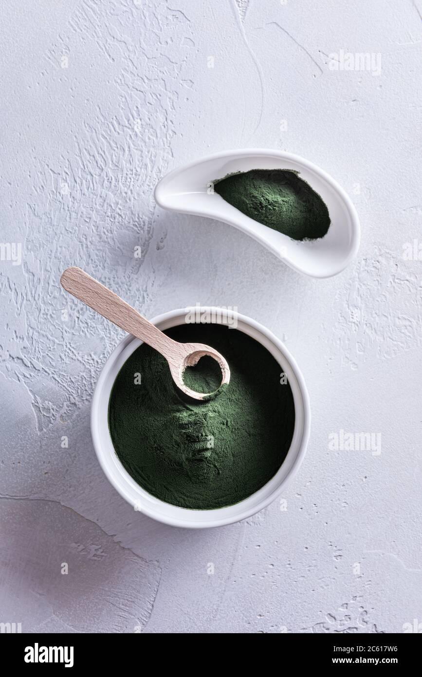 Poudre de chlorelle ou de spiruline verte dans deux bols en porcelaine blanche de forme différente et dans une petite cuillère en bois sur fond blanc. Aliments sains et suralimentaires Banque D'Images