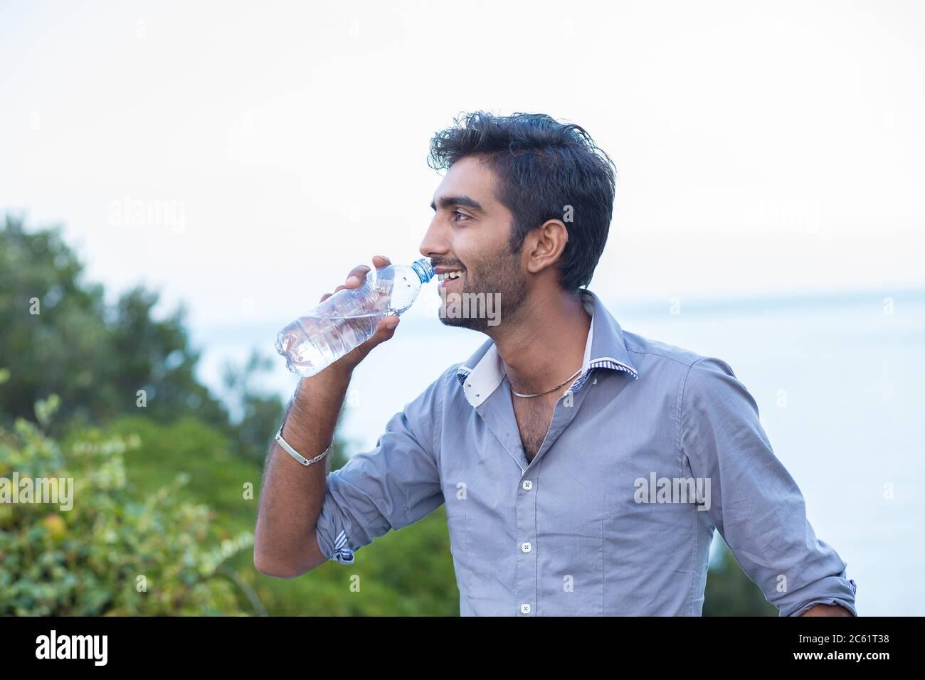 Hydratez-vous. Homme souriant en profil sur le point de boire d'une bouteille d'eau isolé nature arbres et fond de mer Banque D'Images