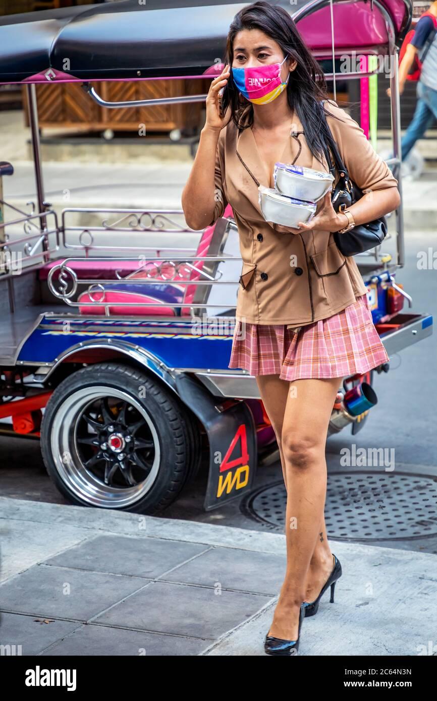 Femme portant un masque de visage parlant sur un téléphone portable et portant des aliments à emporter pendant la pandémie Covid 19, Bangkok, Thaïlande Banque D'Images
