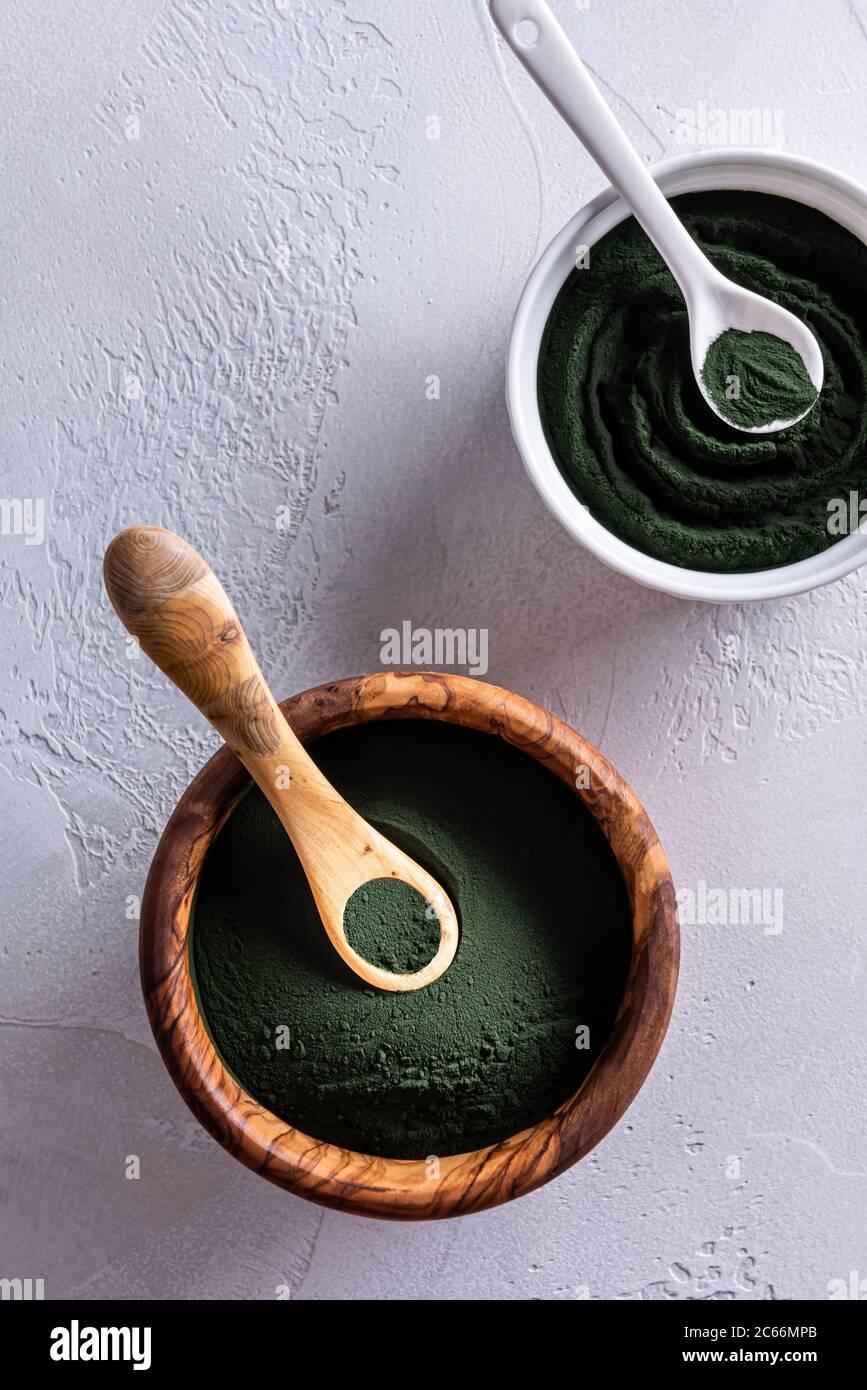 Poudre de chlorelle ou de spiruline dans un bol en bois et dans un bol en porcelaine par le dessus. Les bols sont dotés de cuillères assorties. Alimentation saine et diétine Banque D'Images