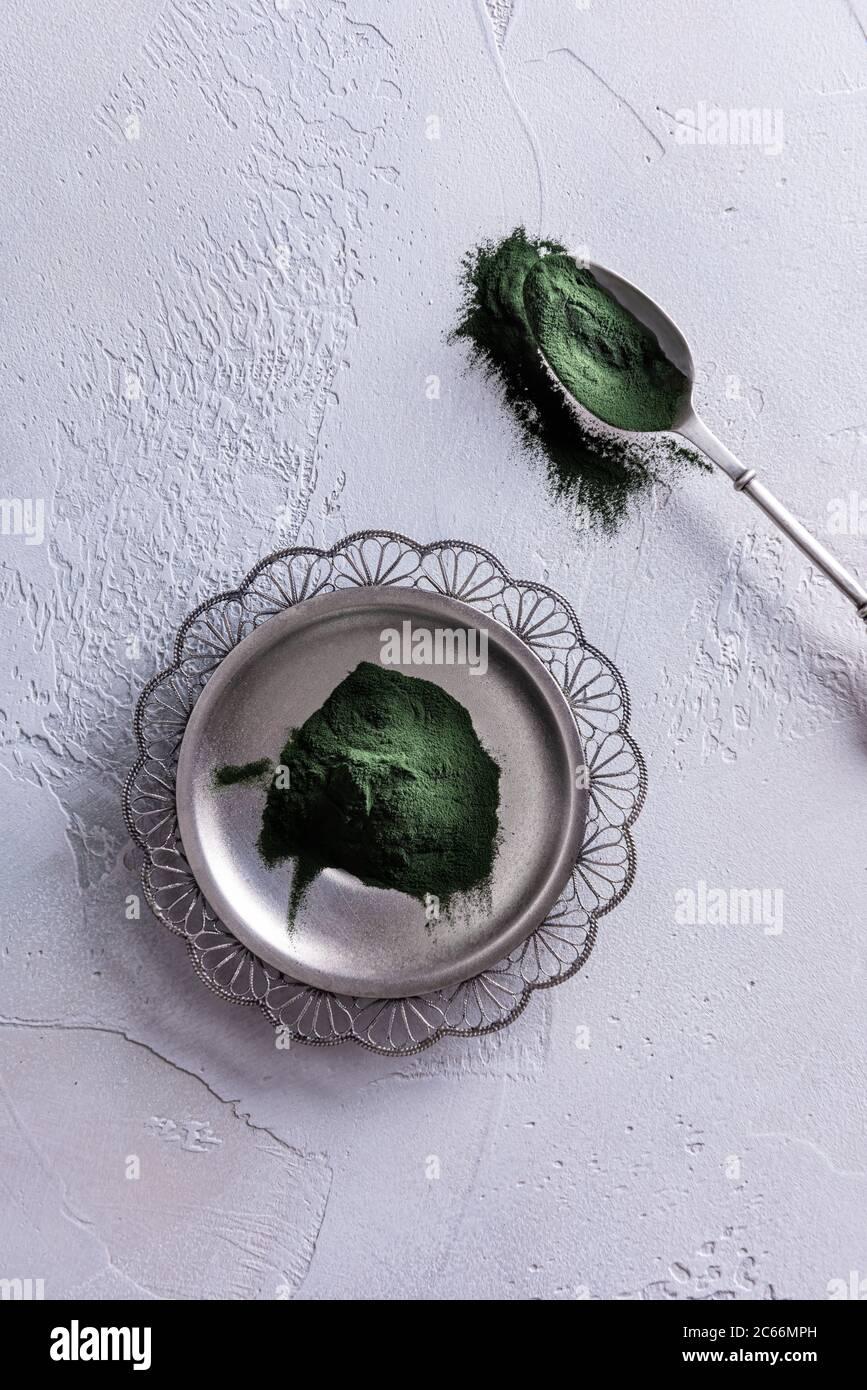 Chlorella vert naturel ou poudre de spiruline sur la plaque d'argent par le dessus et dans la cuillère d'argent près. Concept de nourriture saine et de régime. Blanc Banque D'Images