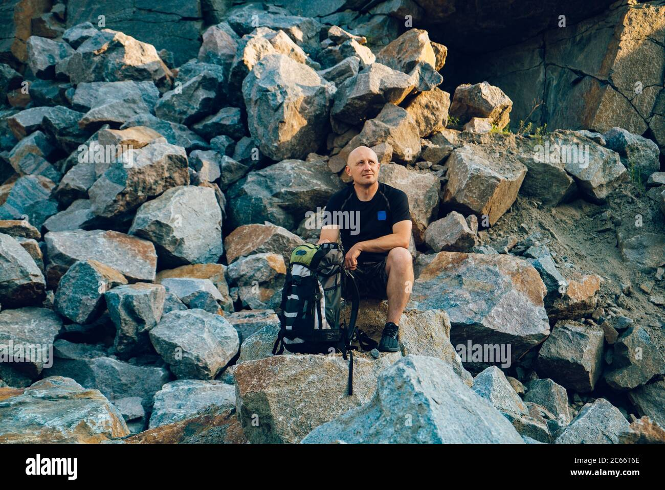 un voyageur repose sur une pierre et regarde le bord autour de lui. Un touriste se trouve sur le fond du rocher en été Banque D'Images