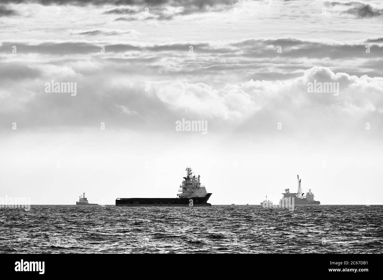 Image en noir et blanc des silhouettes des navires à l'horizon au coucher du soleil. Banque D'Images