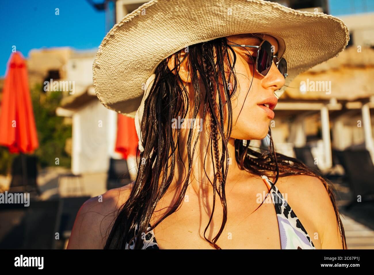 Portrait of happy young woman in swimsuit et beach hat Banque D'Images