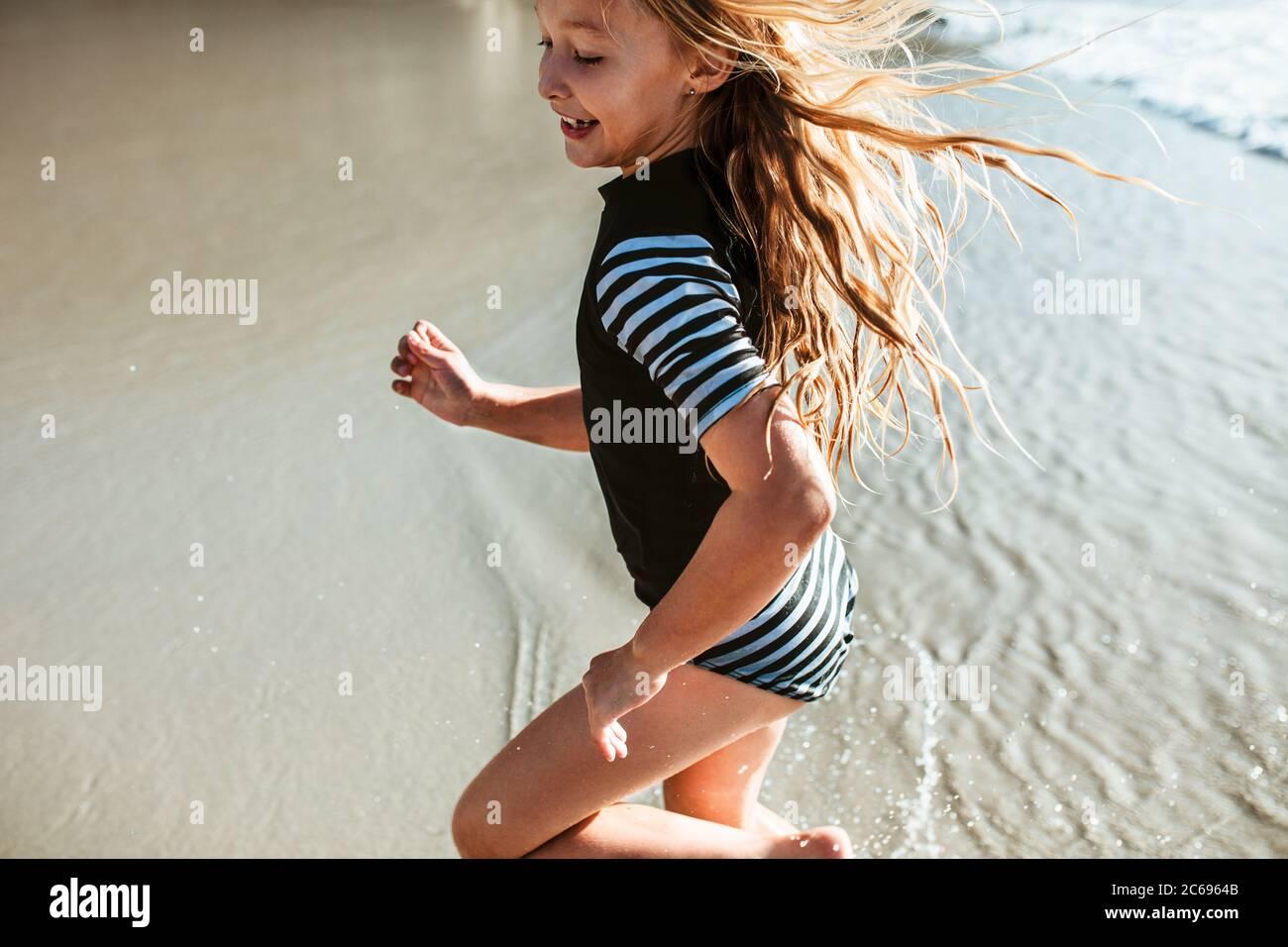 Jolie fille qui court dans l'eau à la plage. Petite fille s'amuser pendant les vacances d'été à la plage. Banque D'Images