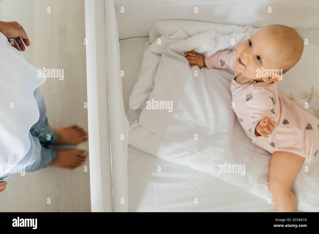 Bébé heureux au lit et jambes de mères. À la maison, intérieur léger. Banque D'Images