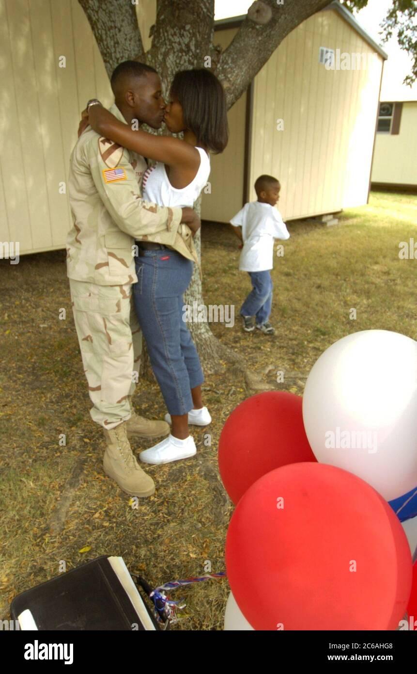Killeen, Texas 28SEP04 : le capitaine Adontis Atkins de la 1re division de Cavalerie de fort Hood embrasse sa femme sous un arbre lors d'une cérémonie de bienvenue à domicile pour 200 soldats stationnés en Irak pendant plus d'un an. ©Bob Daemmrich/The image Works Banque D'Images