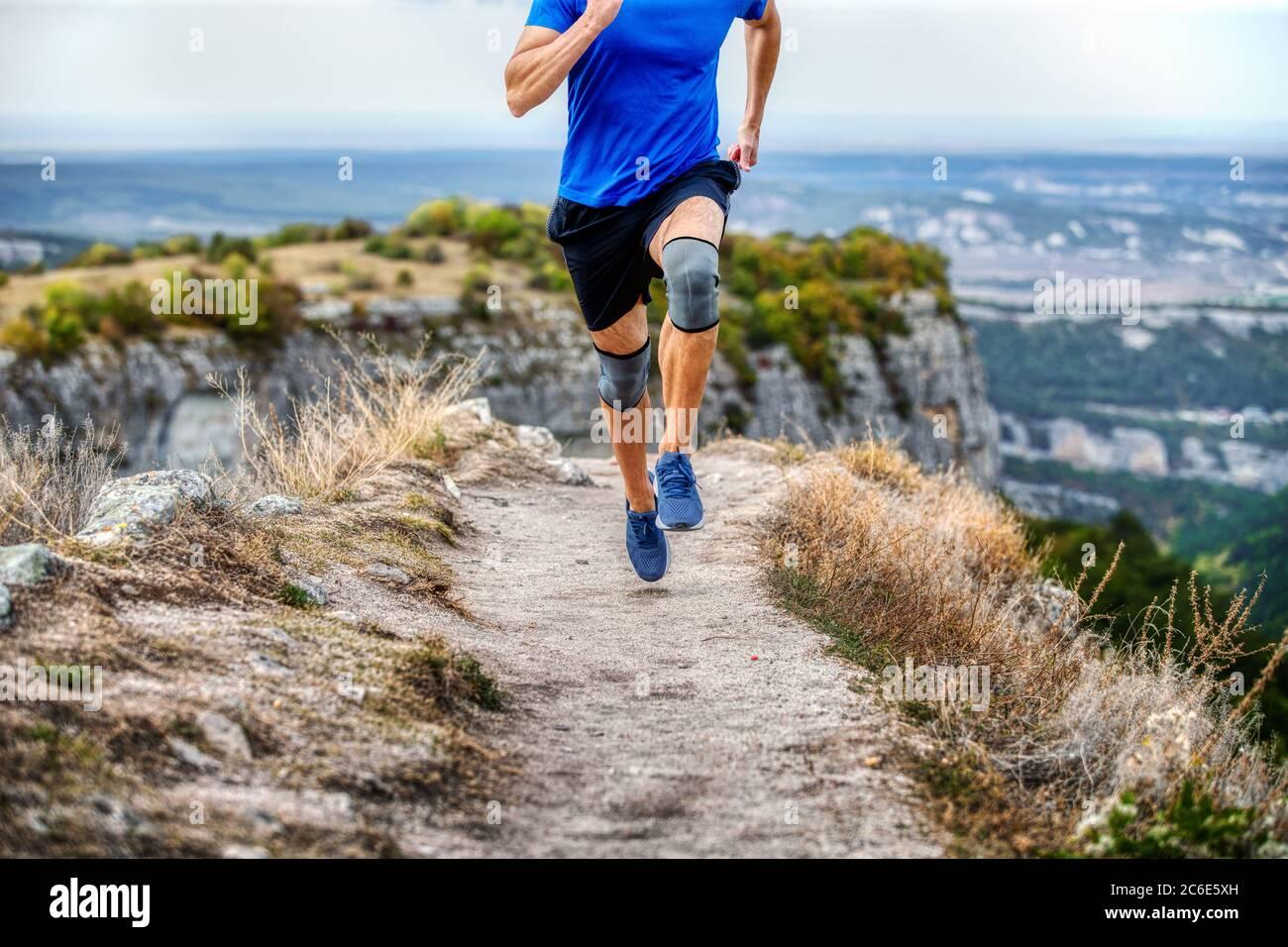 coureur de sexe masculin dans des genouillères sur un chemin de montagne étroit Banque D'Images