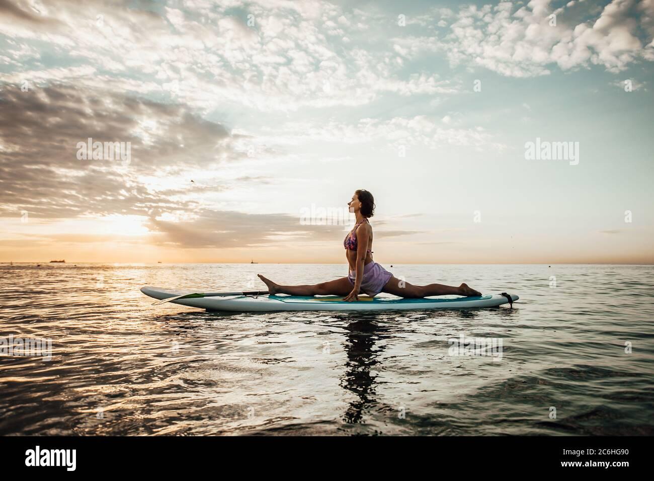 Jeune femme faisant DU YOGA sur un panneau SUP dans le lac au lever du soleil Banque D'Images