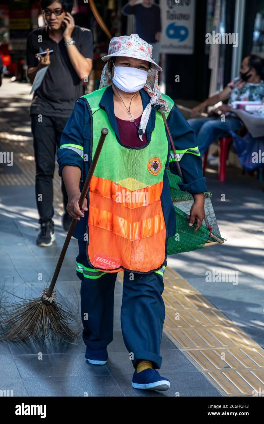 Nettoyant de rue portant un masque et des vêtements haute visibilité pendant la pandémie de Covid 19, Bangkok, Thaïlande Banque D'Images