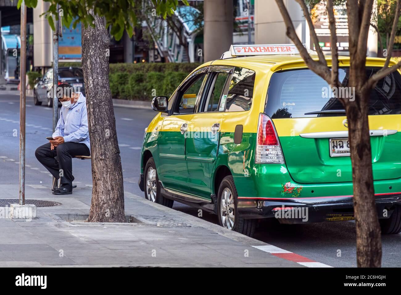 Chauffeur de taxi portant un masque facial utilisant un téléphone portable pendant la pandémie Covid 19, Bangkok, Thaïlande Banque D'Images