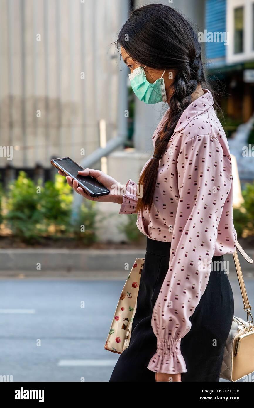 Fille portant un masque facial utilisant un téléphone portable pendant la pandémie de Covid 19, Bangkok, Thaïlande Banque D'Images