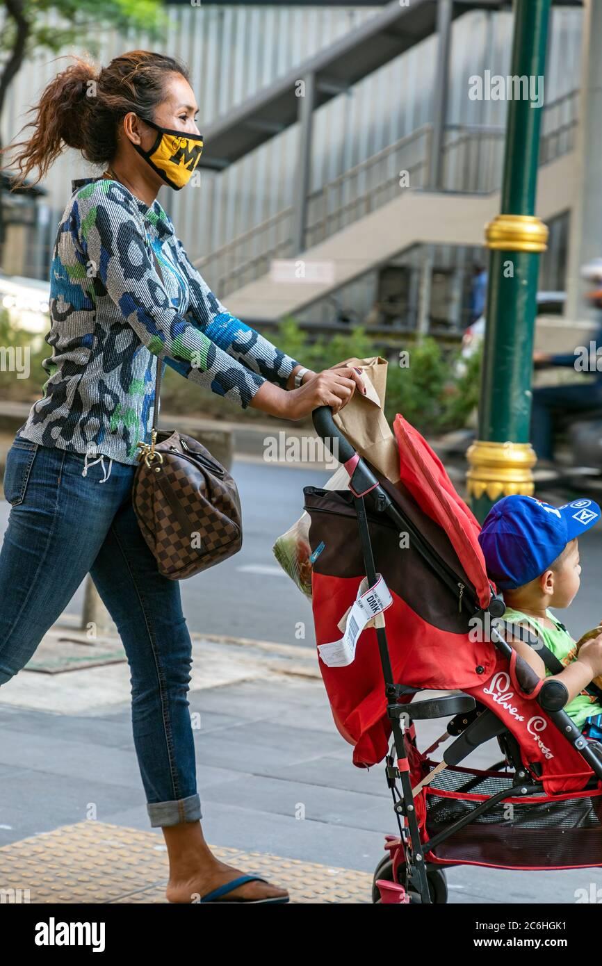 Fille portant un masque de visage poussant la chaise de poussée avec bébé pendant la pandémie de Covid 19, Bangkok, Thaïlande Banque D'Images