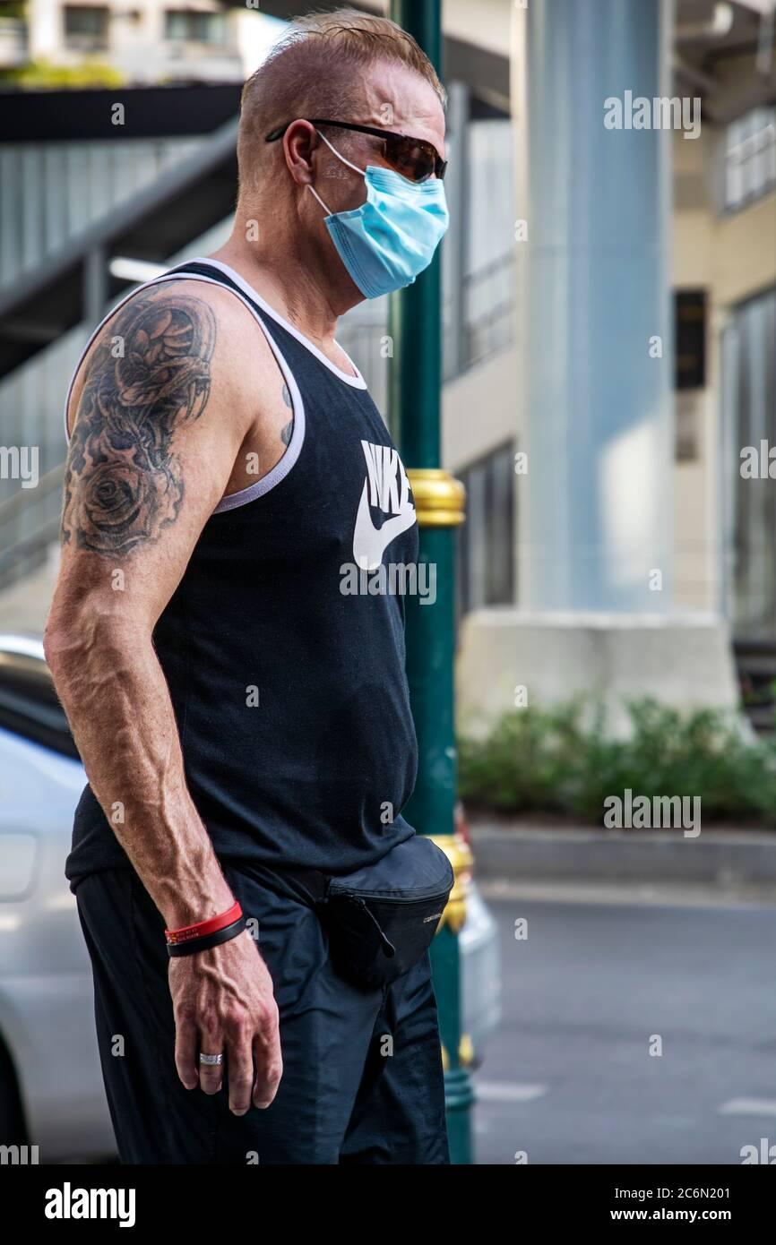 Homme caucasien portant un masque facial et tatouage dans la rue pendant la pandémie de Covid 19, Sukhumvit, Bangkok, Thaïlande Banque D'Images