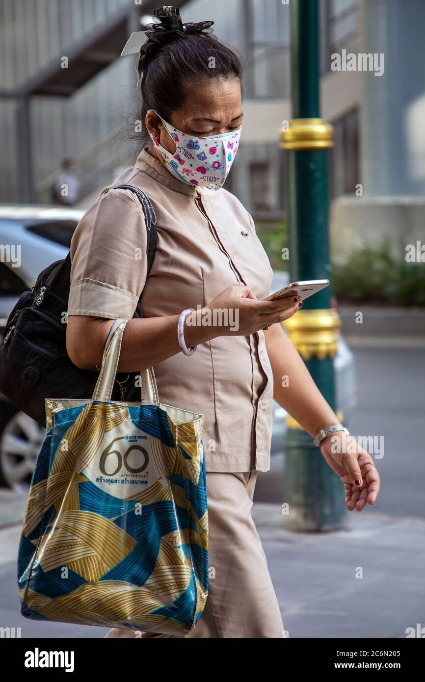 Femme portant un masque facial utilisant un téléphone portable pendant la pandémie Covid 19, Sukhumvit, Bangkok, Thaïlande Banque D'Images