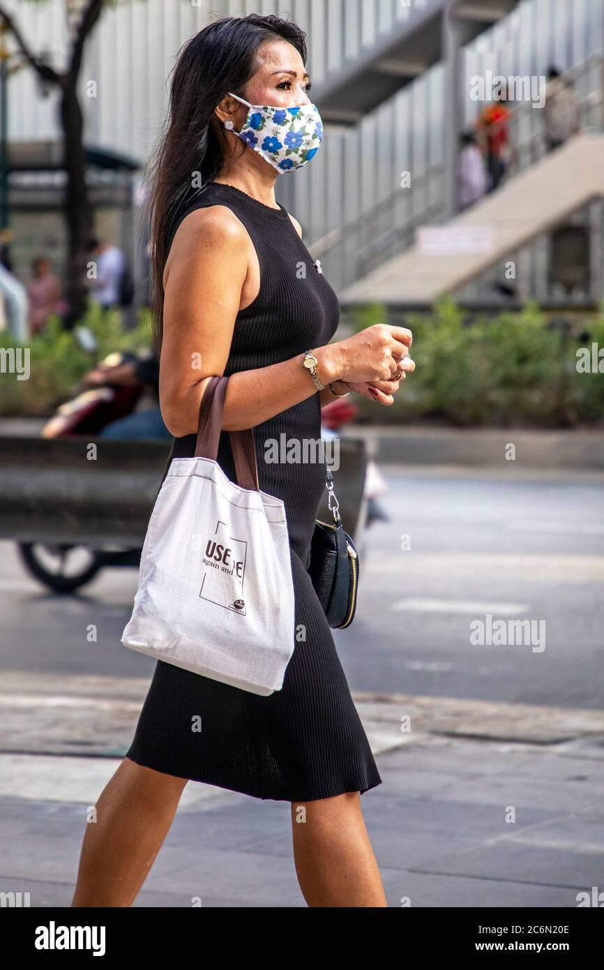Dame avec masque facial et sac de shopping recyclé marchant dans la rue pendant la pandémie Covid 19, Sukhumvit, Bangkok, Thaïlande Banque D'Images