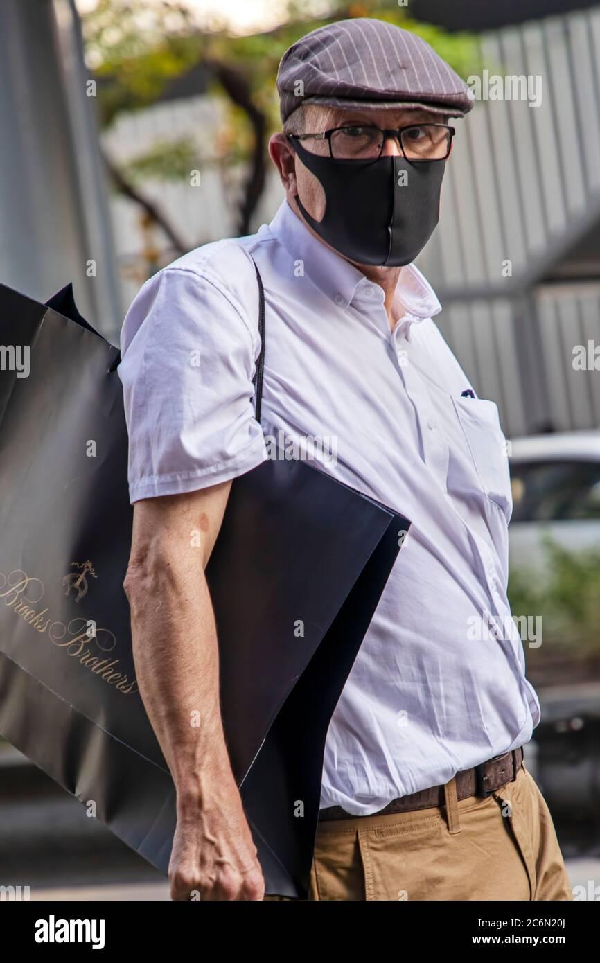 Homme caucasien portant un masque facial dans la rue pendant la pandémie de Covid 19, Sukhumvit, Bangkok, Thaïlande Banque D'Images