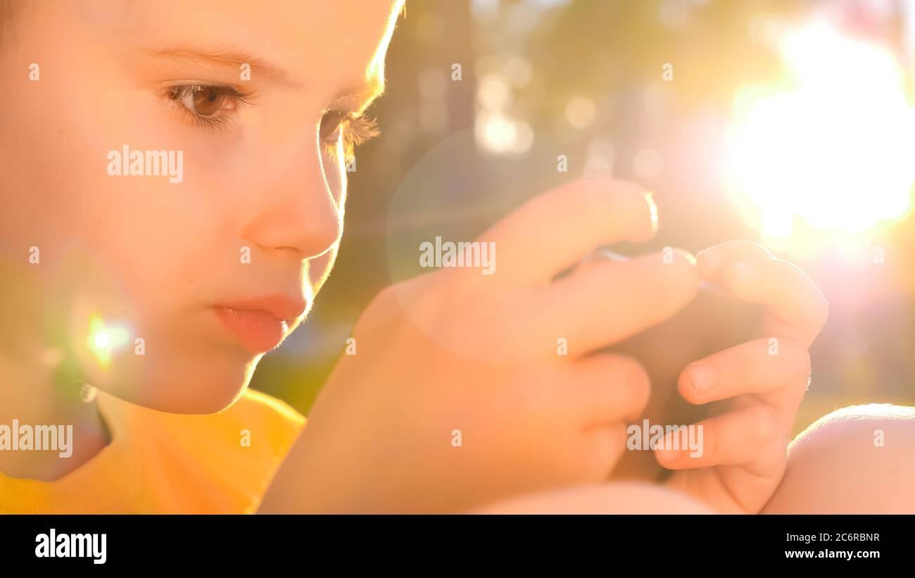 Jeune joueur jouant sur mobile. Enfant avec smartphone. Enfants et technologie. Jeu en ligne, arrière-plan de l'application mobile. Génération de technologie Banque D'Images