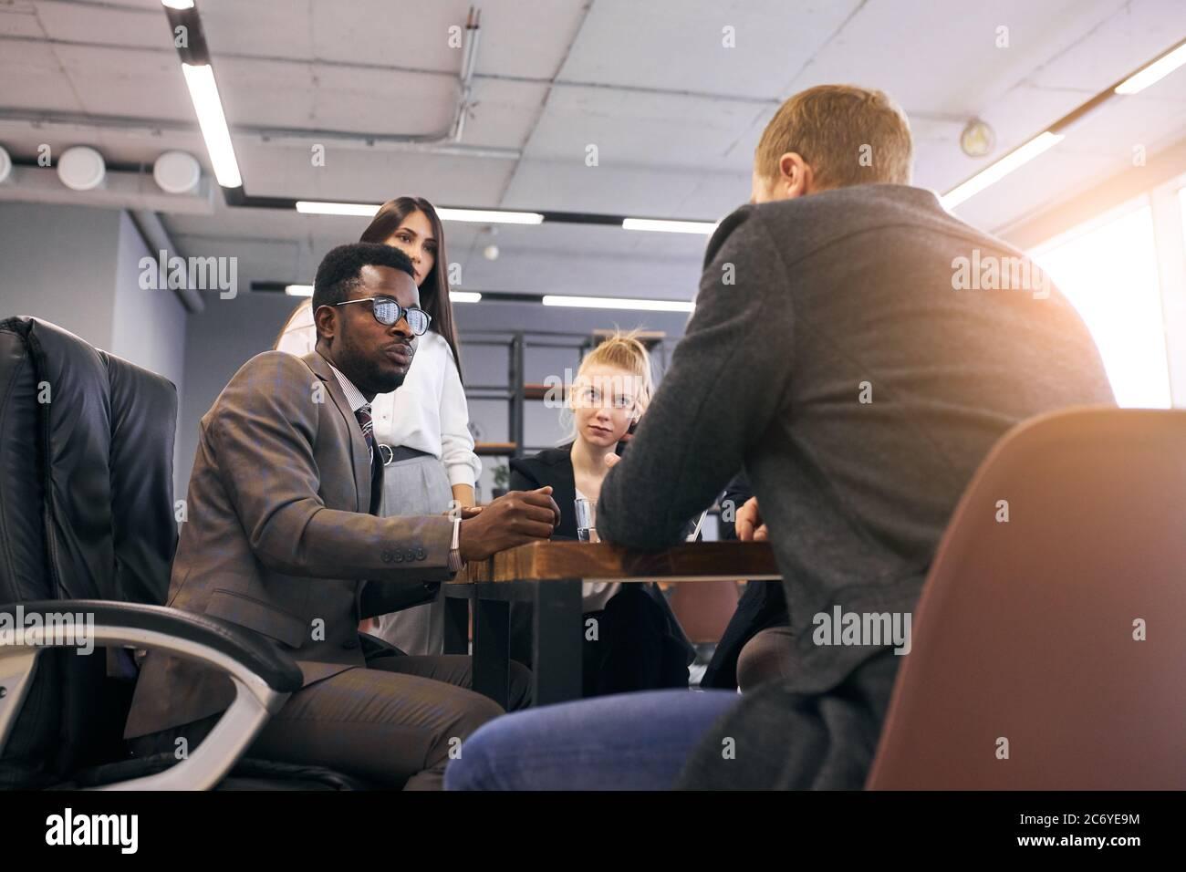 Un homme africain portant du tuxedo s'assoit en parlant avec un homme caucasien tandis que d'autres les écoutent. Travail d'équipe dans le centre d'affaires Banque D'Images