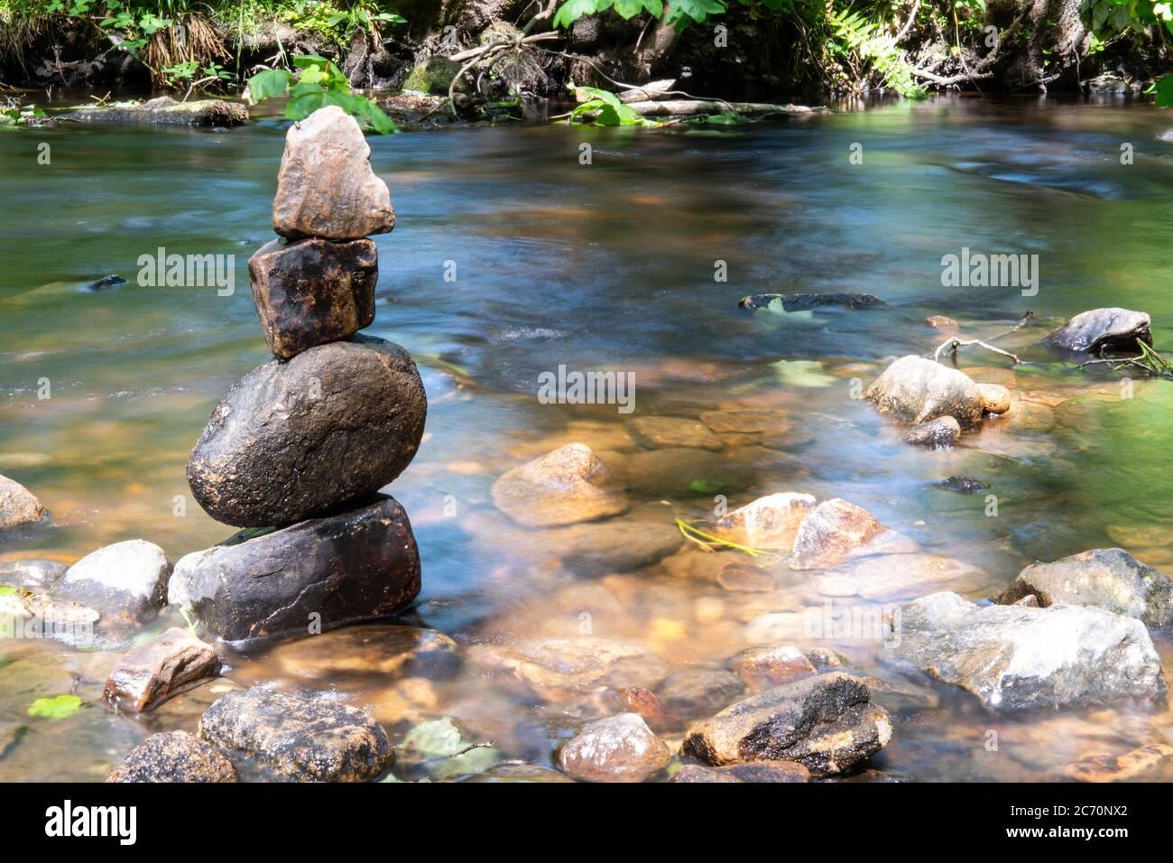 Roches zen équilibrées au bord de la rivière à la vallée de Rivelin près de Sheffield dans le South Yorkshire. Sélectionnez mise au point, exposition longue. Banque D'Images